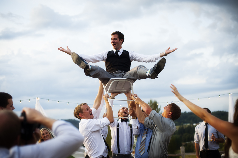Portrait of groom on chair hoisted in air by Ripe Photography.