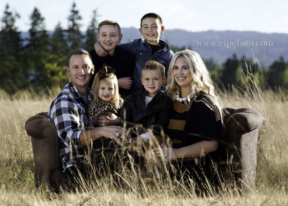 Portrait of family on couch in field by portrait photographer Ripe Photography of Portland, Oregon.