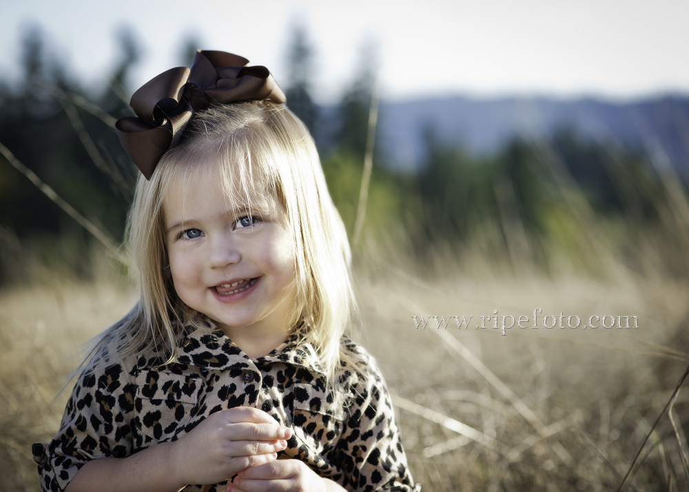 Portrait of little girl in field by portrait photographer RIpe Photography.