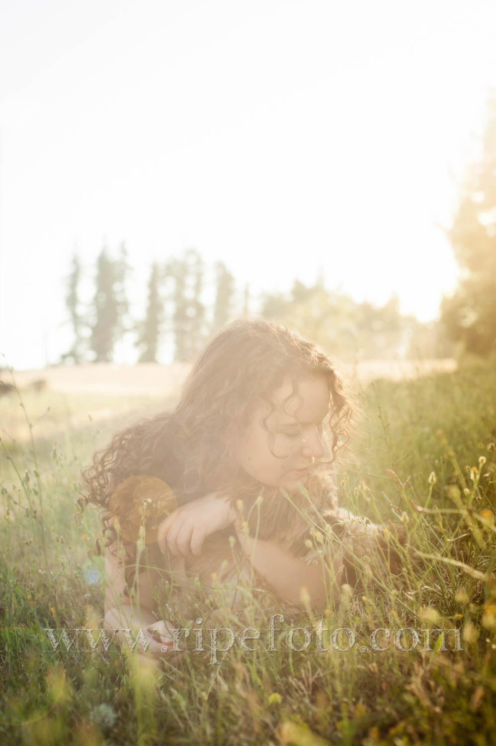 Portrait of teen and her puppy in a field by senior portrait photographers at Ripe Photography in Portland, Oregon.