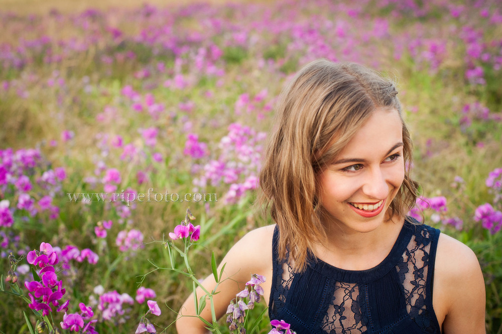 High school senior portrait of girl in field of flowers by senior portrait photographers at Ripe Photography in Portland, Oregon.