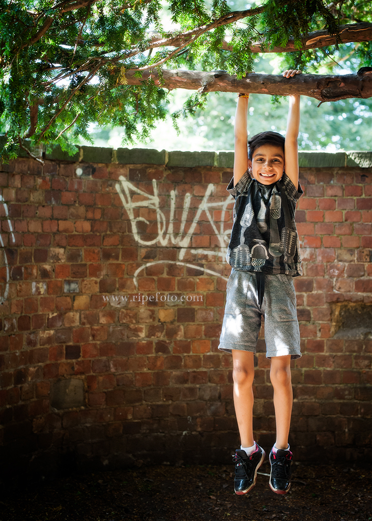 Portrait of boy on brick background by children's photographers at Ripe Photography in West Yorkshire, England.