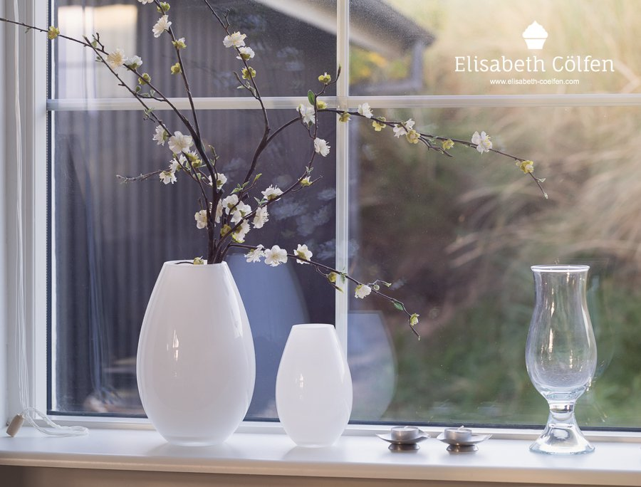 Bouquet of artificial cherry blossoms and vases in a window in a holiday home at the beach