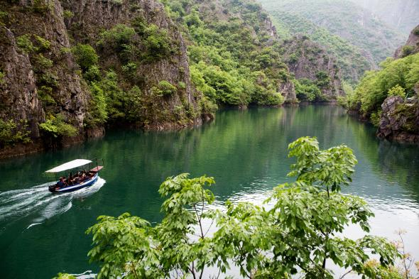 A boat glides past the emerald landscape in Matka Canyon. PHOTOGRAPH BY IMAGES & STORIES, ALAMY STOCK PHOTO