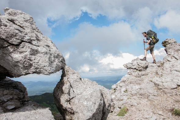 Picture of a hiker on the Via Dinarica trail in Slovenia A hiker looks out to the Adriatic Sea from the summit of Slovenia's Snežnik mountain.  PHOTOGRAPH BY LOIS PARSHLEY, NATIONAL GEOGRAPHIC