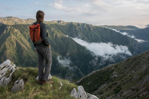 A hiker soaks in the view from an overlook above Rakitnica Canyon in the central mountains of Bosnia and Herzegovina.  PHOTOGRAPH BY LOIS PARSHLEY, NATIONAL GEOGRAPHIC