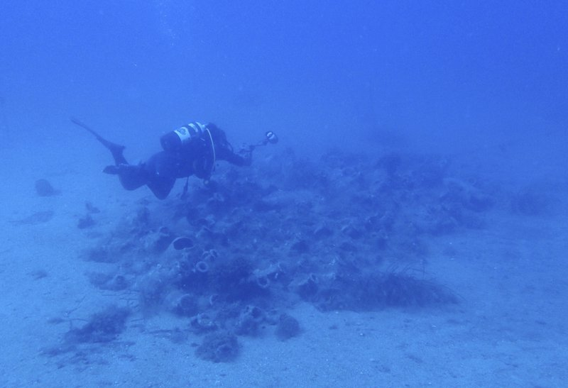 a diver takes photographs of amphorae from a 4th century A.D. shipwreck off the coast of Albania. On the seabed off the rugged shores of Albania, one of the world's least explored underwater coastlines, lies a wealth of treasures. Ancient amphorae that carried olive oil and wine; wrecks with hidden tales of heroism and treachery from two world wars; spectacular rock formations and marine life. (AP Photo/Elena Becatoros)