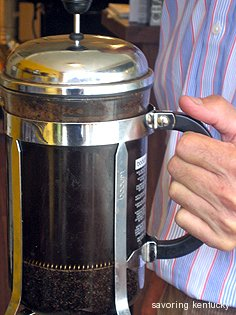 Mark Newberry of Caffe Marco holds full Bodum French Press pot of a light roast blend