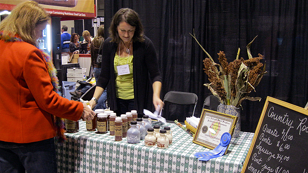 Jill Rock introduces an interested patron to delicious Country Rock Sorghum