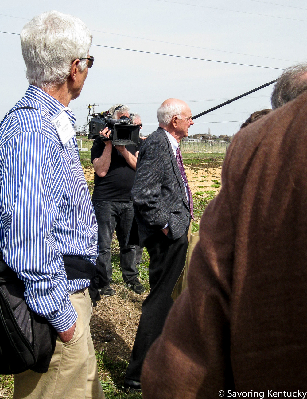 Wendell Berry, center, in a crowd of conference participants touring one site of the St. Catharine's unfolding Berry Farming and Ecological Agrarianism Program.