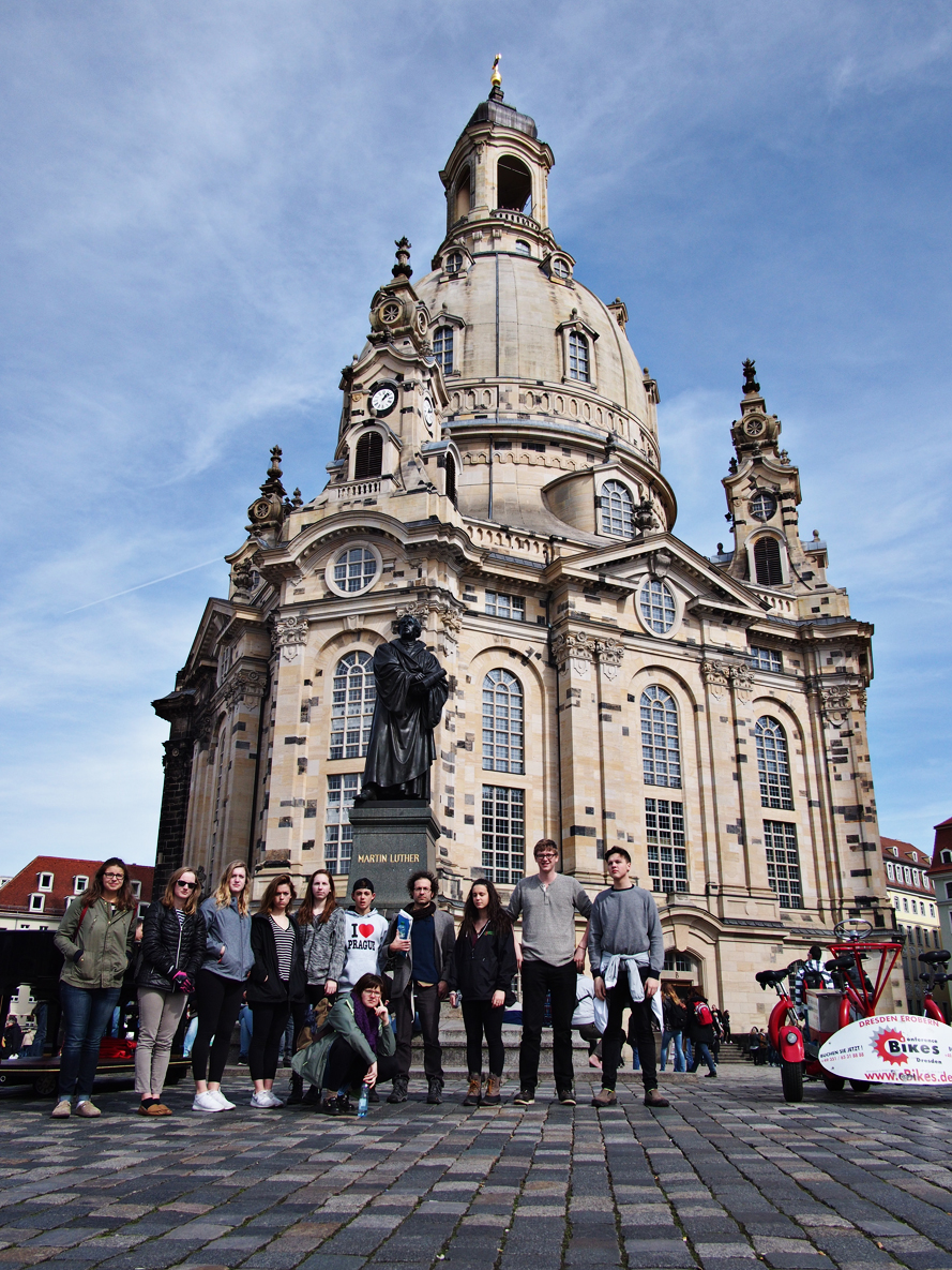 Our intrepid travelers take a moment for a group shot with Martin Luther in front of the rebuilt Frauenkirche. Note the dark stones in the church which are hallmarks of the firebombing during WWII.