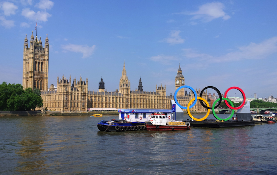 Giant Olympic Rings passing the beautiful Parliament building as it floats down the Thames.