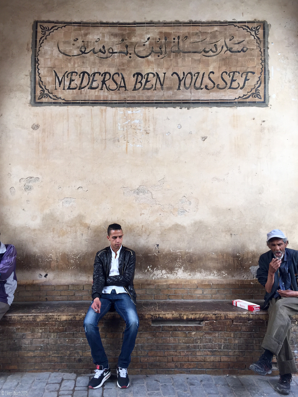 Men sitting outside of Ben Youssef Madrasa (also spelled Médersa Ben-Youssef), once the largest Islamic college in North Africa.  坐在 Ben Youssef Madrasa 外小歇的居民,這兒曾是北非最大的 伊斯蘭神學院。