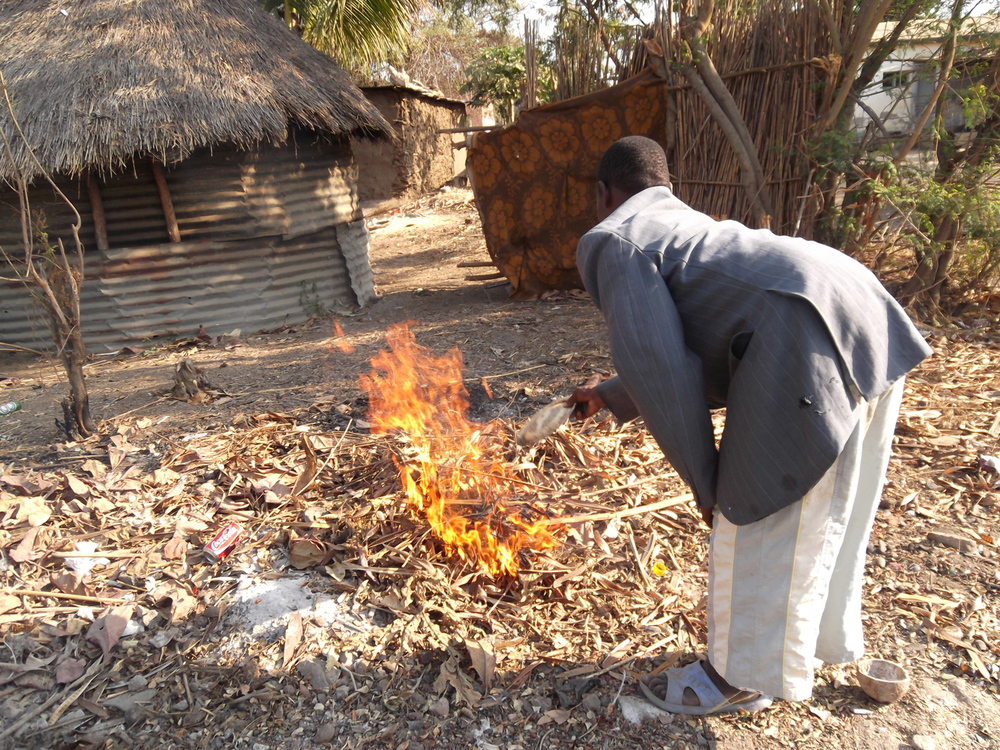 Here I am clearing rubbish from the ground around the house and burning it.  © Fabião António Tivane 2012 / ODI / PhotoVoice