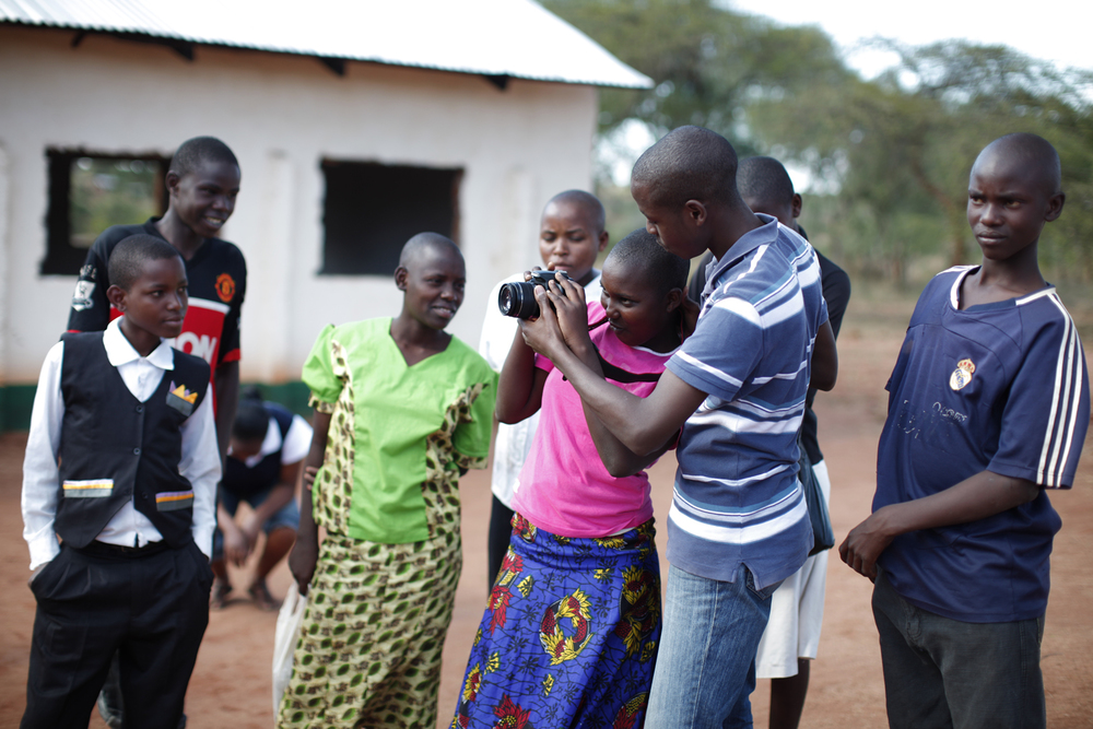 Samuel guides a group of participants in using their new camera skills, Kwakavisi, Kenya.  © Lucy Williams 2012 / ODI / PhotoVoice