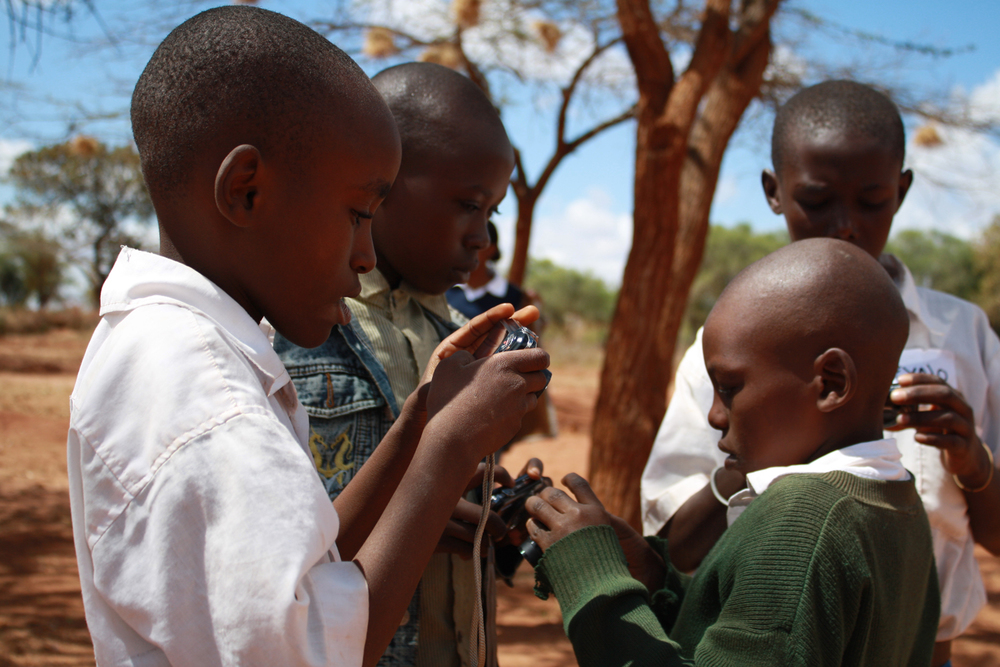 Boys aged 10-14 years getting to grips with the cameras, Kwakavisi, Kenya  © Lucy Williams 2012 / ODI / PhotoVoice