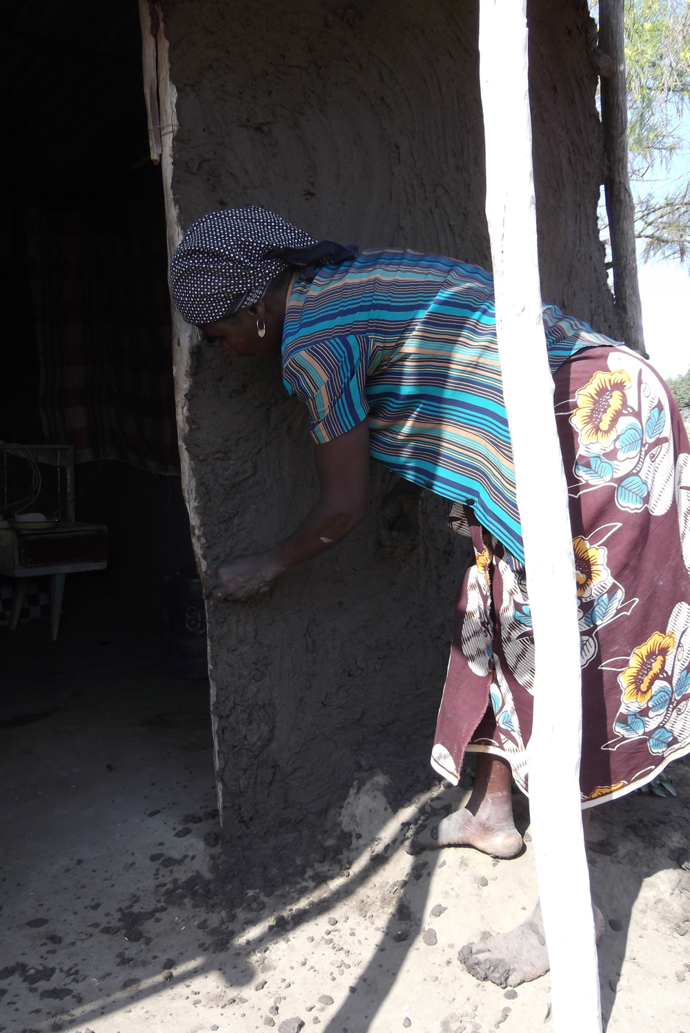My home is made of mud and becomes damaged oftern. Thus lady is fixing it with fresh mud. My little sister will pay for this work.  © Carlito Albino Numbiza 2012 / ODI / PhotoVoice