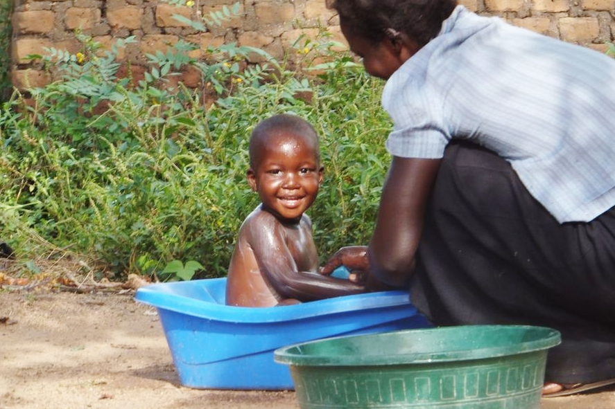 The daughter of a Senior Citizen Grant (SCG) beneficiary bathing her son in Nyaravur sub-county, Nebbi District. © Alex Bagabo 2012 / ODI
