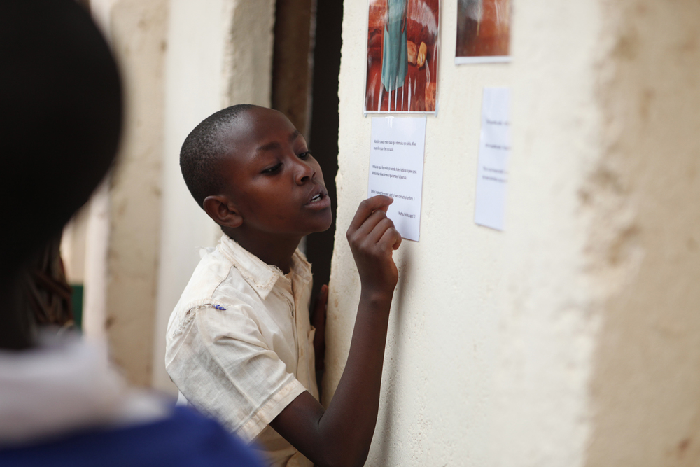 A school friend reads the text under a photo at the community celebration, Kwakavisi, Kenya.  © Lucy Williams 2012 / ODI / PhotoVoice