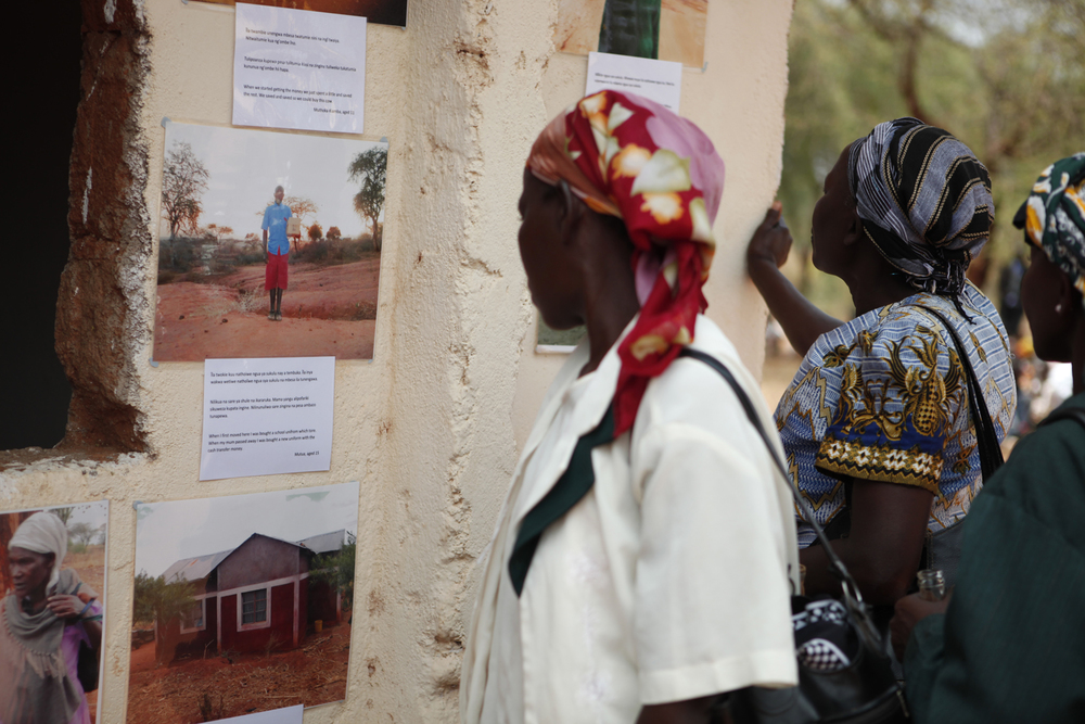 A community member admires the photographs taken by the young people, Kenya.  © Lucy Williams 2012 / ODI / PhotoVoice