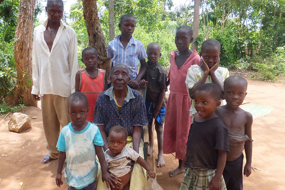 Beneficiary grandmother with her nine grandchildren outside her home, Kenya.  © Beryl Oyier 2012 / ODI
