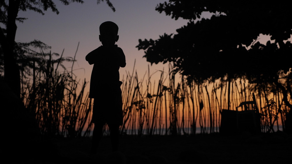 A young boy stands in the sunset in the yard of the Anse à Pitre orphanage, Haiti. Photo Credit: Robert Tully Carr
