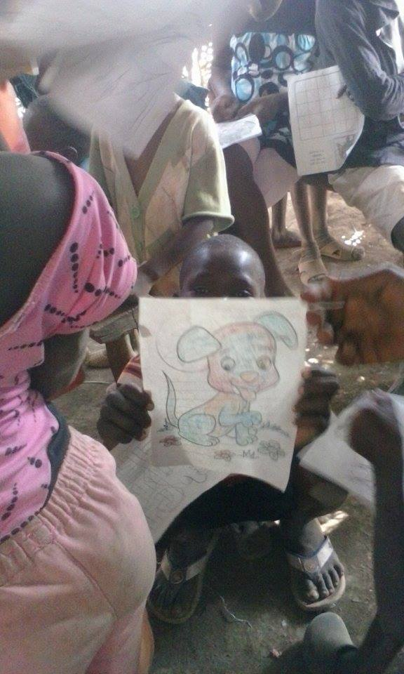 "A young boy holds up his coloring page in a refugee camp near Anse à Pitres, Haiti. Photography by Volmar ""Eddy"" Jonas."