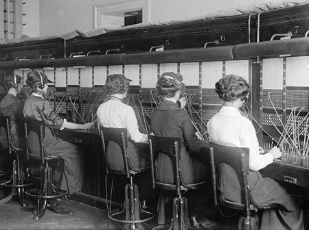 Photo credit: Public domain, Library of Congress #LC-DIG-hec-04117, 1914 Telephone Operator Bank.