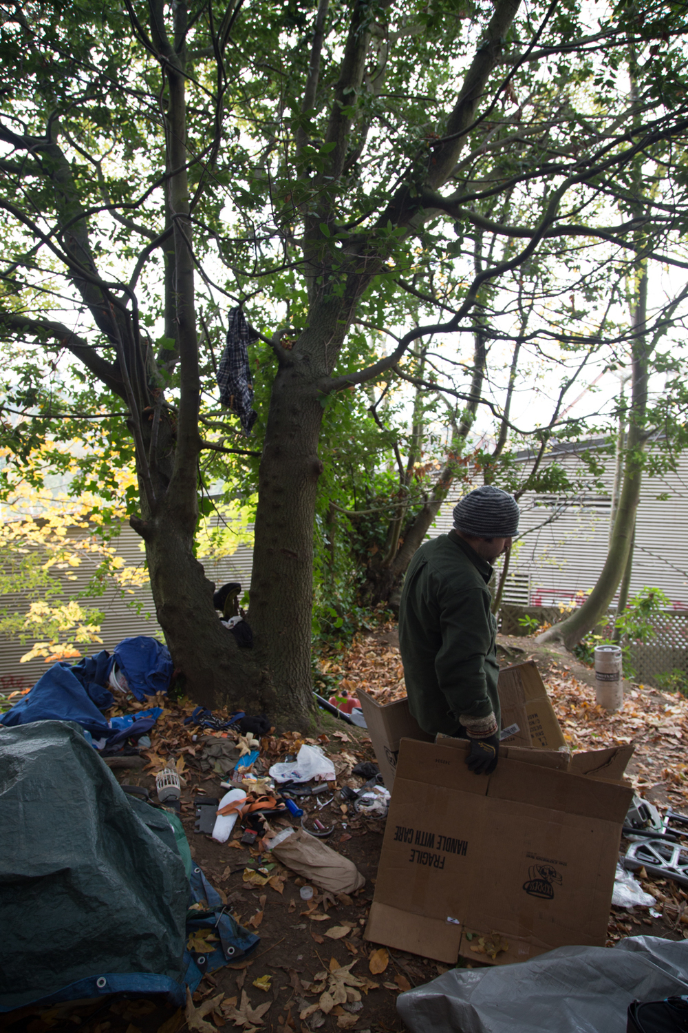 Justin, a resident of the Ballard Locks encampment, breaks down and moves his belongings as a city clean up crew evicts them from their location.