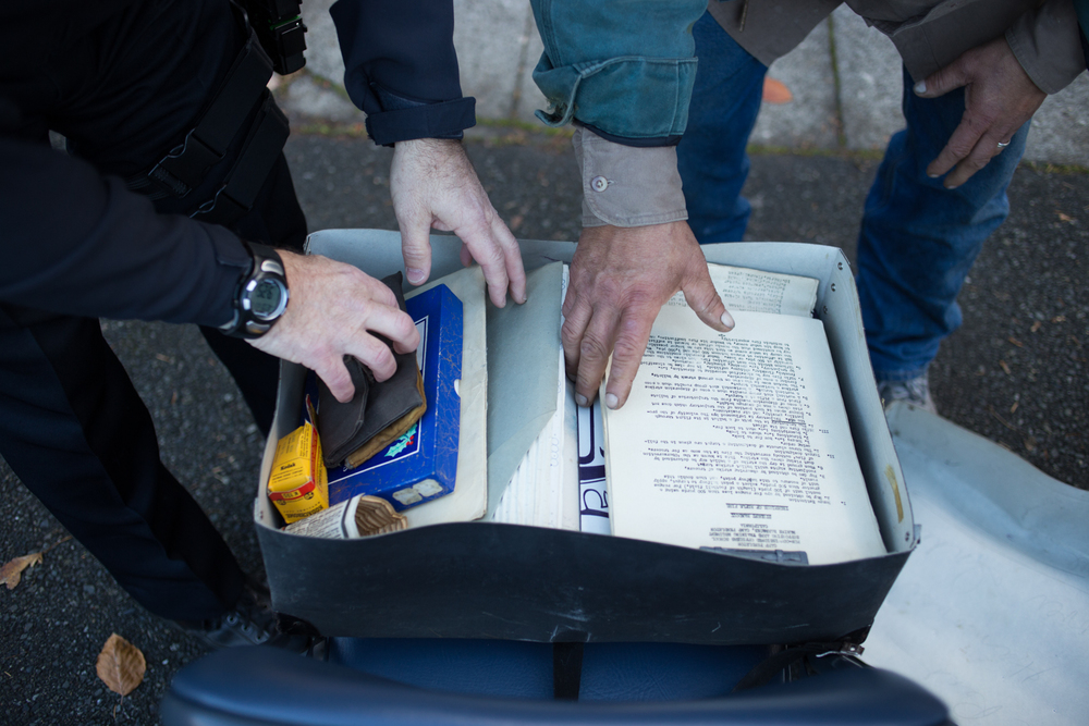 Officer Wear goes through a box of belongings from a recent deceased homeless man. Inside the box were letters, scraps books, military field guides and Marine Decorations. Seattle, WA