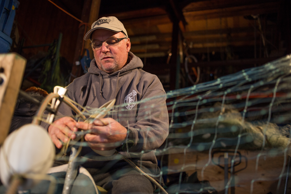 John Mcdonald Hangs a gillnet in his locker at Fisheman's Terminal