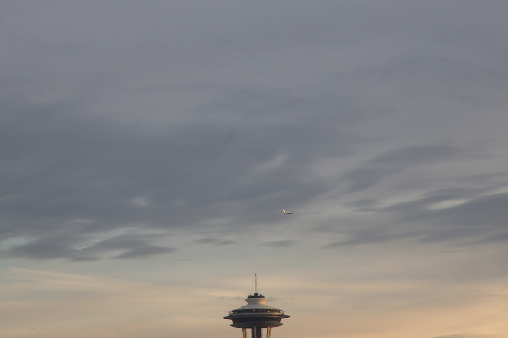 A plane makes its way past the Space Needle. Machinists and Boeing have yet to reach a compromise that will bring a 777x manufacturing line to Western Washington, where Boeing is headquartered. The company has received bids from other states for the contract to build the plane. Seattle, WA
