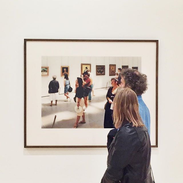A picture of people in a museum looking at a picture of people in a museum looking at art.