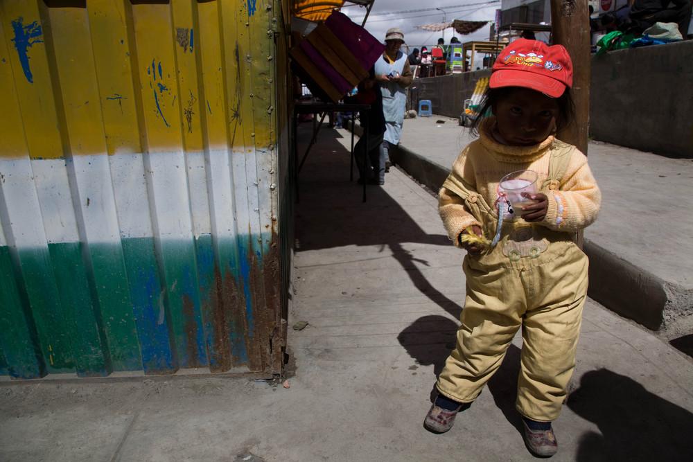 Niña sucia en amirillo y sombrero rojo.  Ananea, Peru.