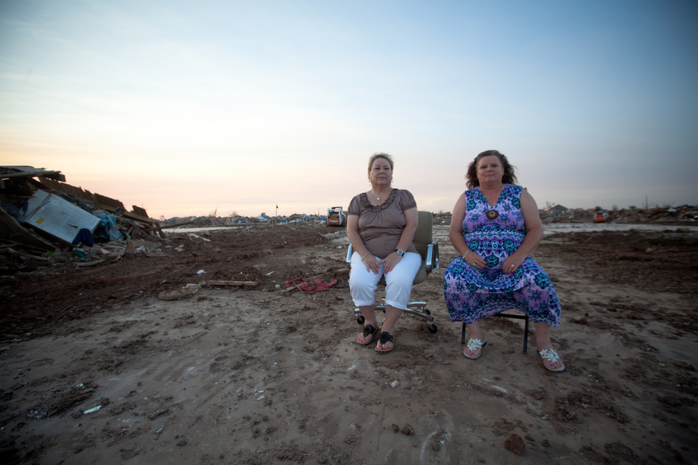 "German natives and longtime Oklahoma residents, Marion Rivera and cousin, Ingrid Jones, sit in Marion's former driveway. Marion boasted about her talent for decorating, ""My house was filled to the gill with stuff, but everything had its place."""