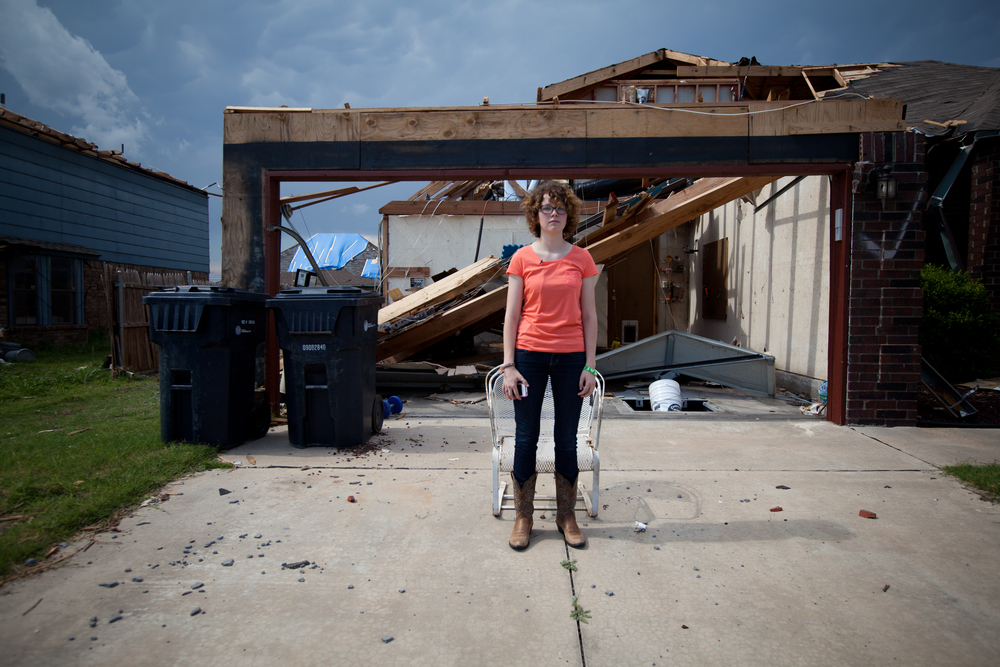 Sarah Goodman, age 18, stands in front of her childhood home which was damaged beyond repair during the tornado. Sarah graduated from Southmoore High School days after the tornado struck. Optimistic at the prospect of a fresh start, Sarah will soon call the freshman dorms home when she begins at University of Central Oklahoma in the fall.