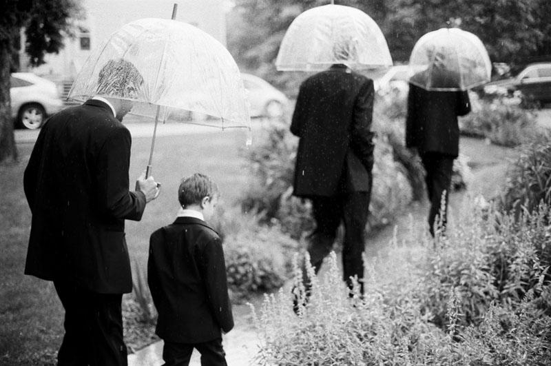 chautauqua-community-house-wedding-bridal-party-rain-umbrellas-guys-walking.jpg