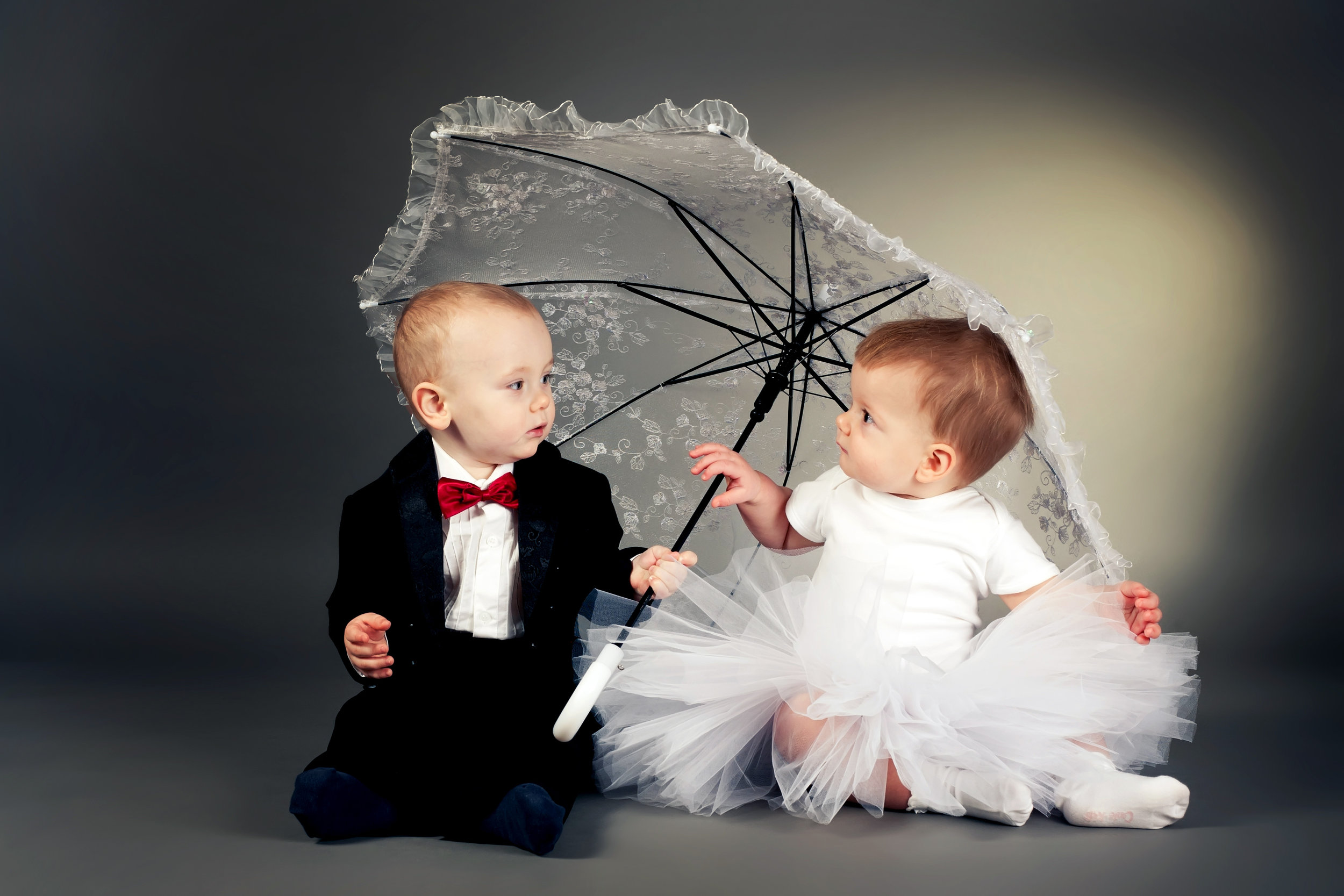 Little bride and groom sitting under an umbrella