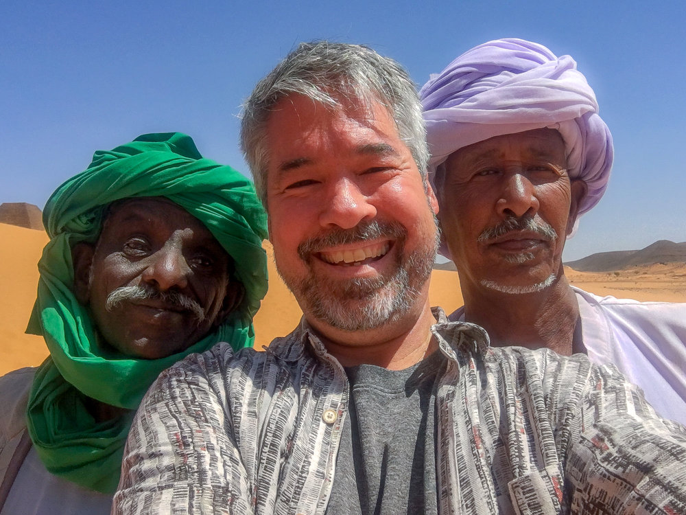 New friends, caretakers at the remote but spectacular Meroe Pyramids - long-ago capital of the Nubian Kushite Kingdom rising mirage-like from the desert sands 200 km NE of Khartoum, N Sudan.