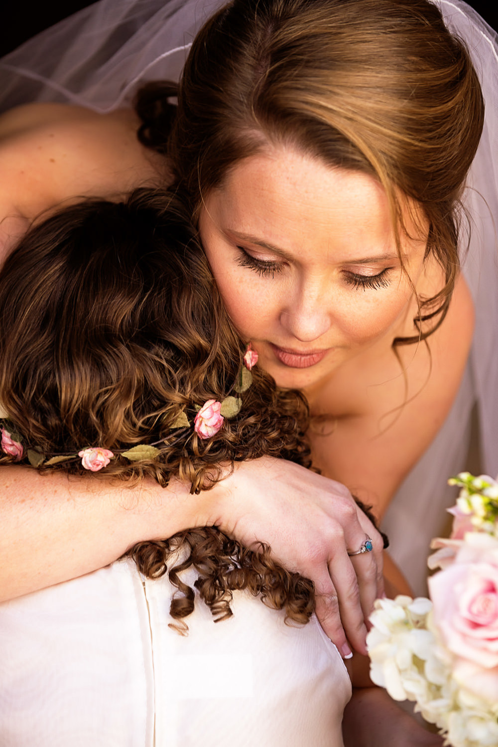 The bride giving her flower girl a big hug. Rustic and intimate backyard wedding in Ojai California