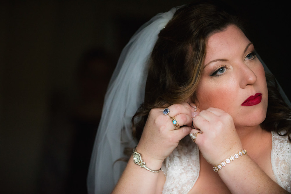 f27-Photography-Ventura-Clocktower-Inn-Wedding-Bride-Putting-on-Earrings
