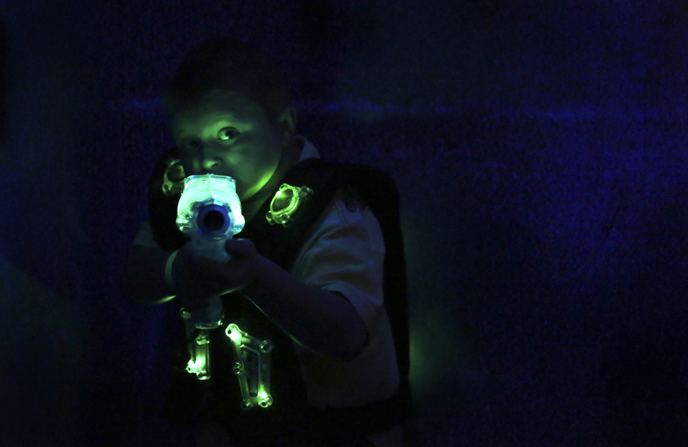Chase Wood, 6, of Syracuse, N.Y. peers around a corner, prepared to shoot while playing laser tag with friends and family at the ShoppingTown Mall in DeWitt, N.Y. on April 5, 2013.