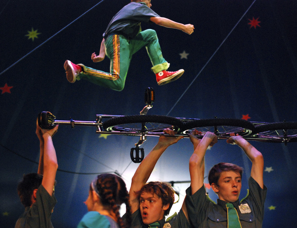 "A performer jumps on a trampoline while others carry a giant unicycle across the stage during Circus Smirkus' ""Oz Incorporated"" in Brattleboro, Vt. on July 16, 2013."