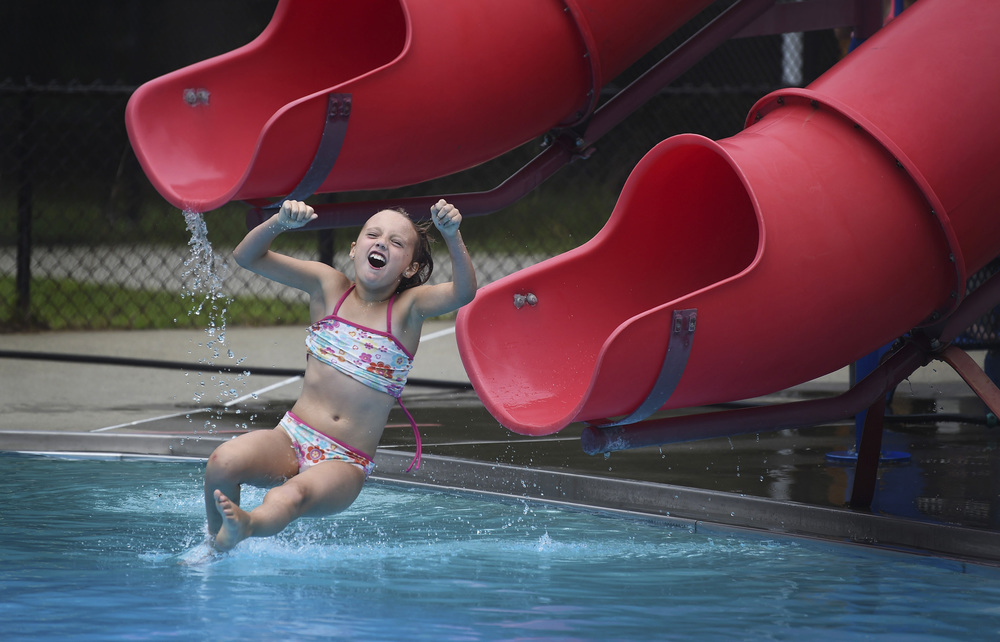 Ava Ferencz, 8, slides into the pool at Living Memorial Park in Brattleboro on August 12, 2014.