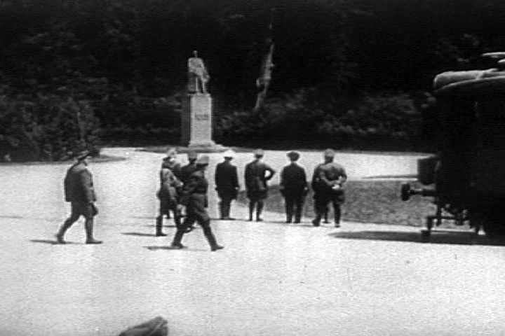 via  Wikimedia Commons  | A still from Frank Capra's film  Divide and Conquer.  Hitler (hand on hip) looks at the statue of Foch before the signing of the armistice on 22 June 1940.