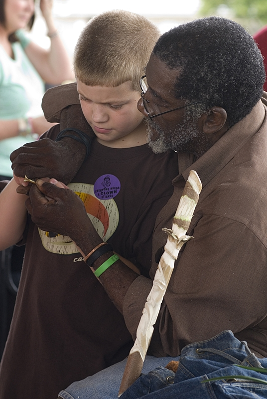 Papa Ulu instructs a young apprentice in the art of wood carving at Riverside Arts Market.