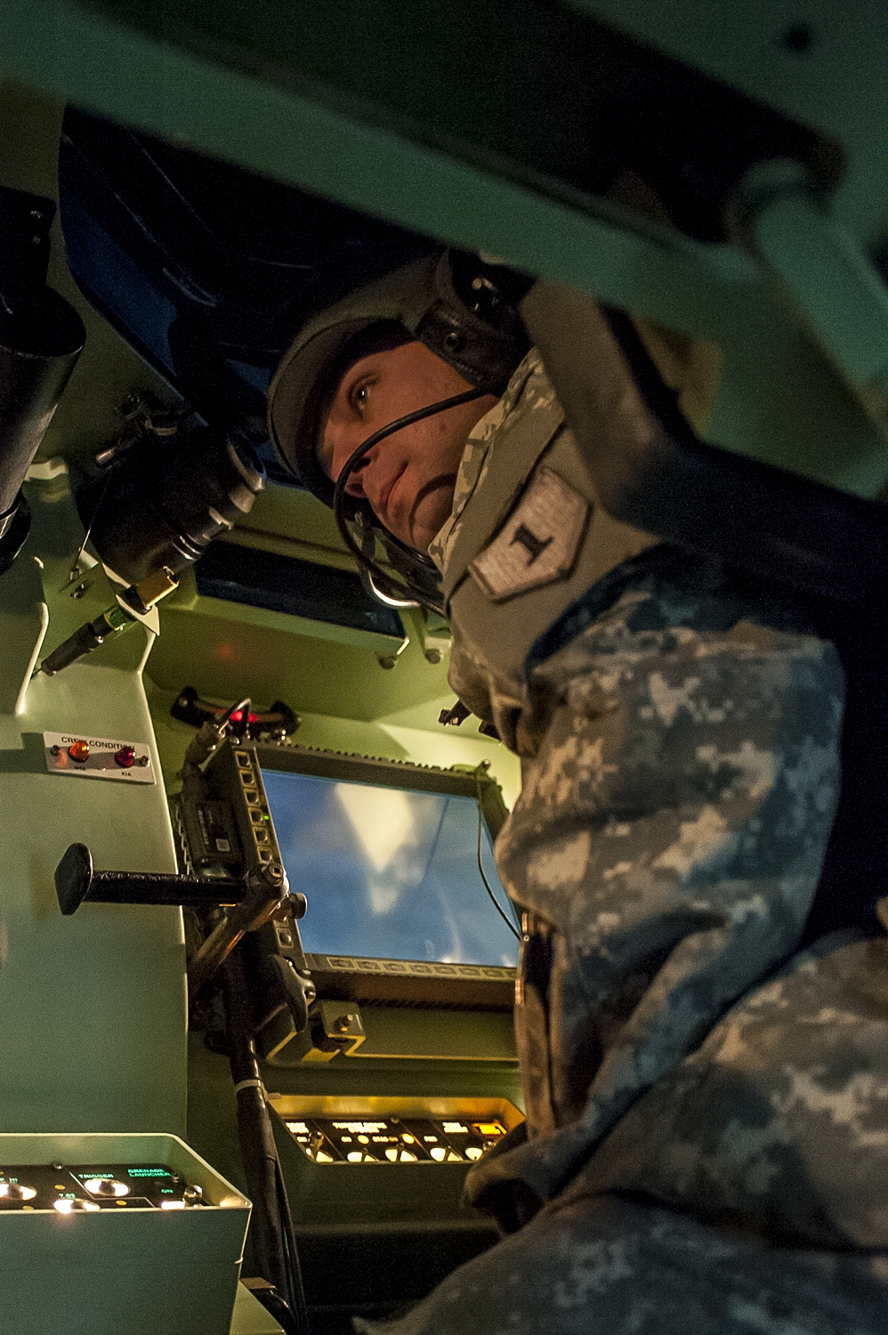 A soldier operates a Bradley Infantry Fighting Vehicle simulator. Soldiers at Fort Riley have begun using a new virtual training system integrating simulators with real life troop and equipment movements, designed to cut costs and better prepare troops.