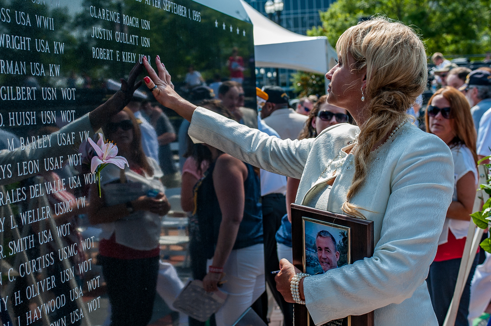 While holding a plaque honoring her husband, Robin Kiely runs her finger through her husband's newly engraved name on the Duval County Veterans Memorial Wall in Jacksonville, FL on Memorial Day. The names of five deceased veterans were added to the wall in a remembrance ceremony at the Wall.