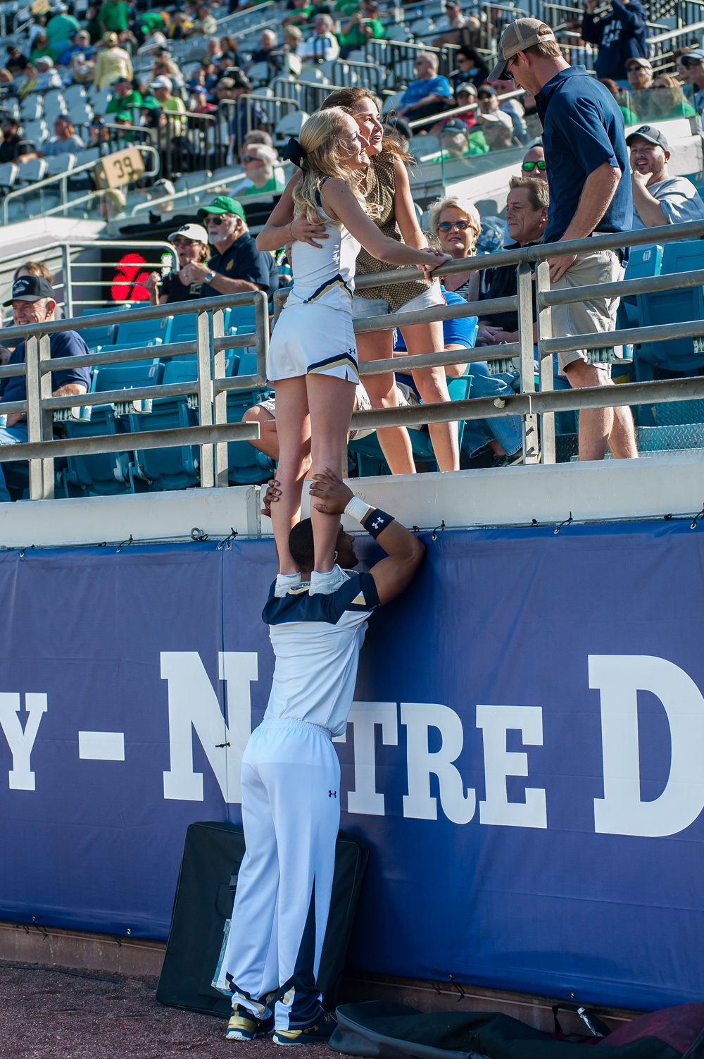 A Naval Academy cheerleader gets a little help from her friend so that she can catch up and take a few selfies with some fans in the stands as the Notre Dame Fightin' Irish took on the Navy Midshipmen at EverBank Field in Jacksonville for a soon-to-be annual rivalry football game played in the River City.