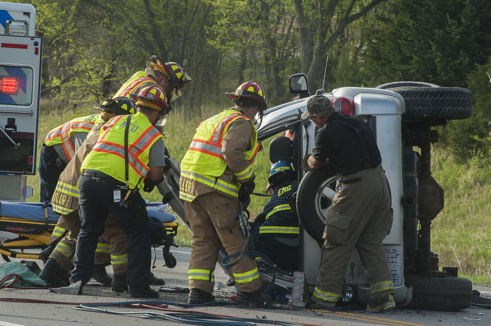 At a two vehicle crash on Tuttle Creek Parkway, a paramedic stabilizes the driver of an up-ended Jeep SUV while firefighters bend back the top of the vehicle to free the trapped driver.